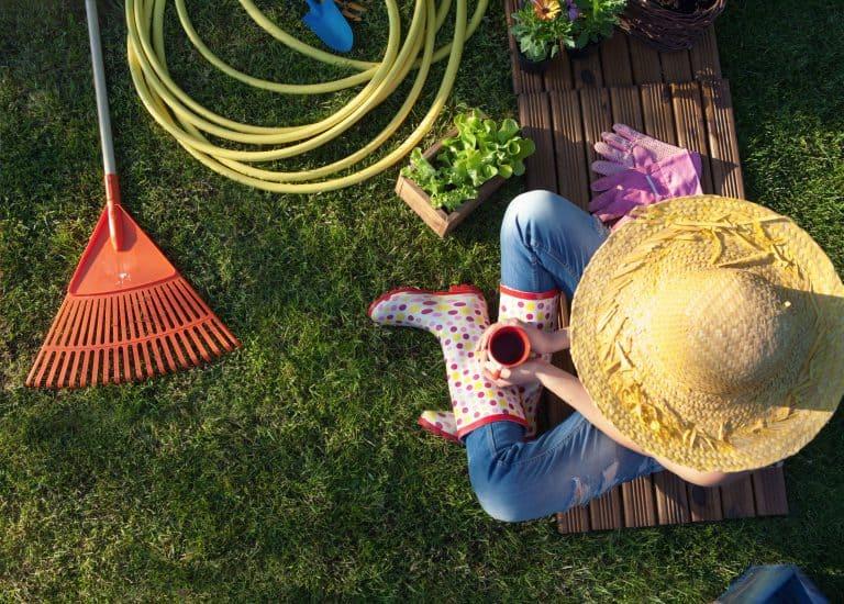 Frau macht eine Pause bei der Gartenarbeit