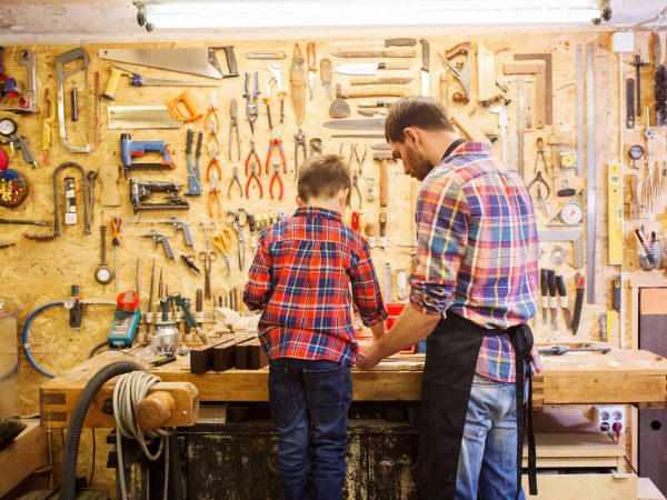 family, carpentry, woodwork and people concept – father and little son working with wood plank at workshop