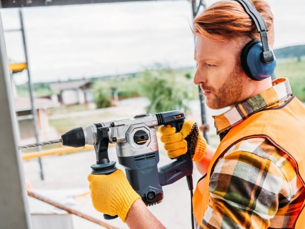 side view of handsome builder in noise reducing headphones using power drill at construction site
