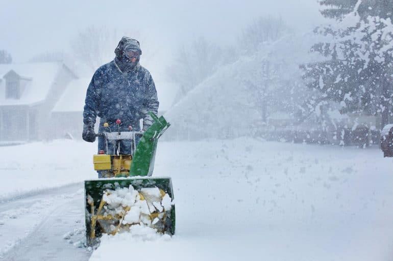 Person bedient Schneefräse